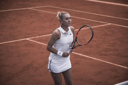 Elena Vesnina wearing the Lacoste Spring Sleeveless Polo, also available in navy, and the Lacoste Spring Drawstring Skirt