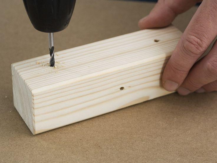 Pasul 2: Găurirea prealabilă a barelor de legătură Cele patru bare de legătură se înşurubează din spate în picioarele tip colţar cu plăcile late pentru picioarele scaunului şi cu cele înguste. În acest scop găuriţi preliminar pe cele două părţi barele de legătură cu maşina de găurit şi burghiul pentru lemn de 5 mm. Aveţi grijă să alternaţi găurile în cruce, dar nu găuriţi niciodată la aceeaşi înălţime, pentru ca şuruburile să nu se lovească unul pe celălalt în bara comună.