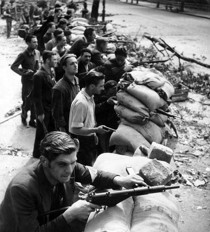 """Caption: """"Members of the French Resistance stand armed behind a barricade during the Liberation of Paris from German forces. It is estimated that between 800 and 1,000 resistance fighters were killed during the battle, and another 1,500 were wounded before the Germans surrendered the city. Paris, Île-de-France, France. August 1944. Image taken by Robert Doisneau."""""""