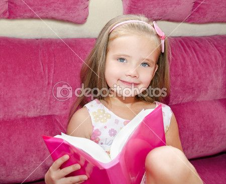 Little girl reading a book and siting on the sofa — Stock Image #30143025