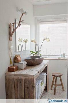 Meuble en bois de récup, vasque en pierre, miroir simple, et lumière naturelle.