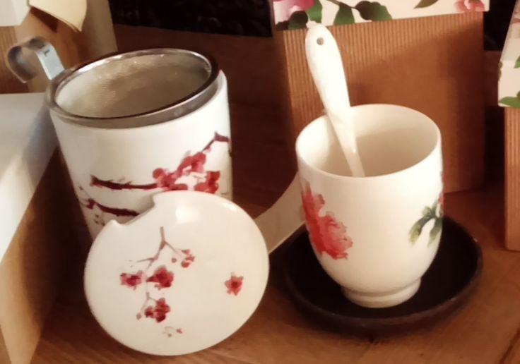 A droite, la tasse solo et la cuillère Darcy Teapot en porcelaine peinte à la main, et sa soucoupe en argile noire. A gauche, la tisanière solo Fleurs de cerisiers comprenant la tasse le couvercleen porcelaine peinte à la main et le panier a infusion en acier inoxydable. Le tout, toujours créé par Alisson Appleton.