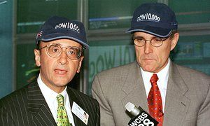 """New York Stock Exchange chairman Richard Grasso and New York City mayor Rudy Giuliani (R) wear """"Dow 10,000"""" hats as the Dow Jones Industrial Average closes above 10,000 for the first time, 29 March, 1999."""