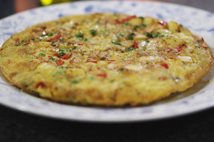 """De tortilla de patatas is wellicht een van de meest beroemde Spaanse gerechtjes. Jeroen maakt zo'n dikke omelet met ui en paprika. Er gaan ook erwtjes bij, en eigenlijk kan je je fantasie de vrije loop laten om een """"tortilla-maison"""" te bedenken. Let er alleen op dat je dit gerecht zacht laat garen. Serveer de tortilla warm of koud, als maaltijd of als hapje. Olé!"""
