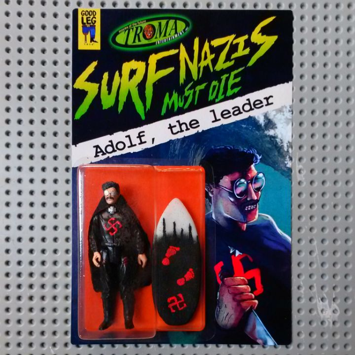 """We're proud to present our first official Troma action figure release, introducing Adolf, leader of the Surf Nazis from Troma's '87 classic """"Surf Nazis Must Die"""" movie! This 3.75"""" resin action figure comes 100% hand made & painted, with 5 points of articulation, cape, surfboard (courtesy of FonkyFingers Fingerboards), and on card featuring art by Pablo Perra & Ralph Niese. Limited to an edition of 35 pieces. SURF'S UP, GUYS! AND SURF NAZIS MUST DIE!!! $85"""