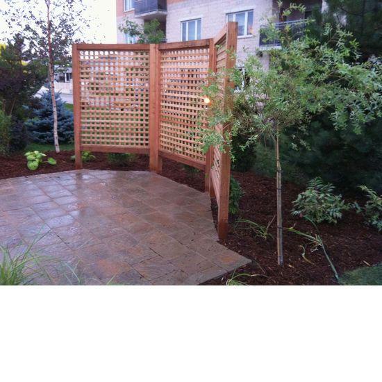 Custom lattice privacy fence with custom stone patio