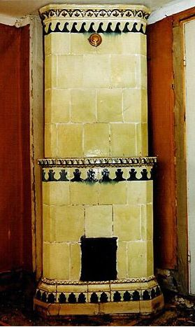 Yellow-green tiled stove with a mantle, ca 1830. Decorations in blue and brown. Height 245 cm.
