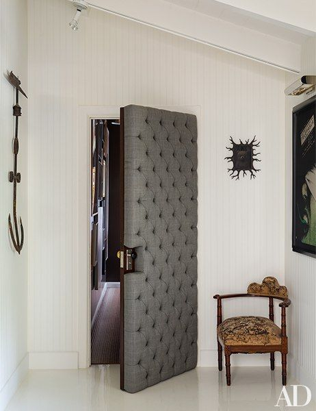 Button-tufted suiting fabric upholsters the door between Kopelman's suite and a hall to the home's master bedroom. A small Mark Ryden painting in a hand-carved frame hangs above an antique English chair; the anchor, at left, is also antique.