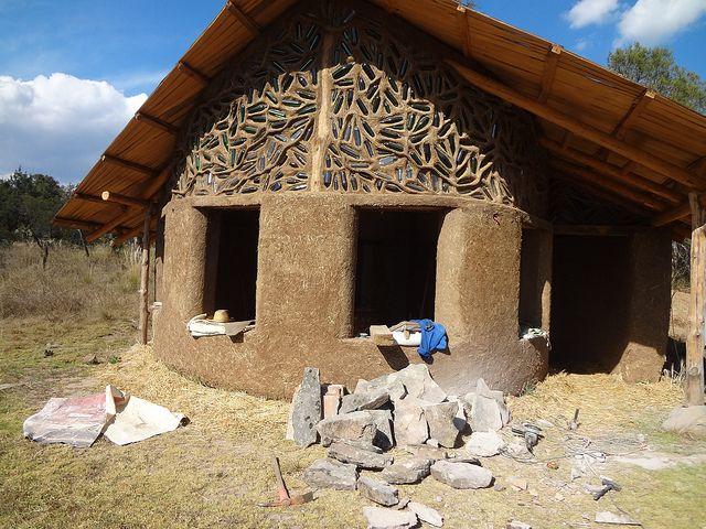 Construcci n de adobe y paja base en piedra techo de madera y botellas de vidrio incrustadas - Piedras para construccion ...