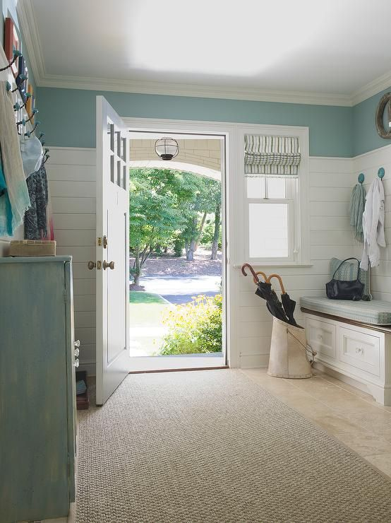 White and blue cottage mudroom features a built-in…