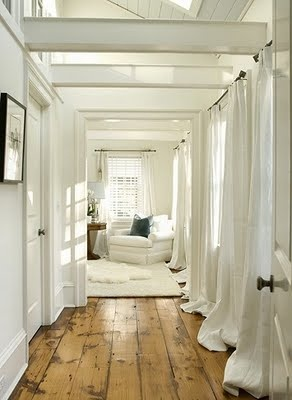Bunched white curtains, whitewashed ceilings, lots of natural light, beach house feel