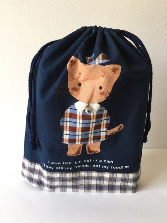 SANRIO - WINKI PINKI DRAWSTRING BAG - Winki Pinki is so adorable! Too bad you dont see her around anymore... :( - This drawstring bag can be used to store all your precious treasures! - The bag is made of Navy blue light canvas and plaid cotton fabric - Attached is a small working bell at Winki Pinkis collar - The front says:  I love fish, but not in a dish...  They are my friends, not my food!  - The back says:  Winki Pinki - 13 length 10.5 wide 2 wide at the base - 1991 - Produced by…