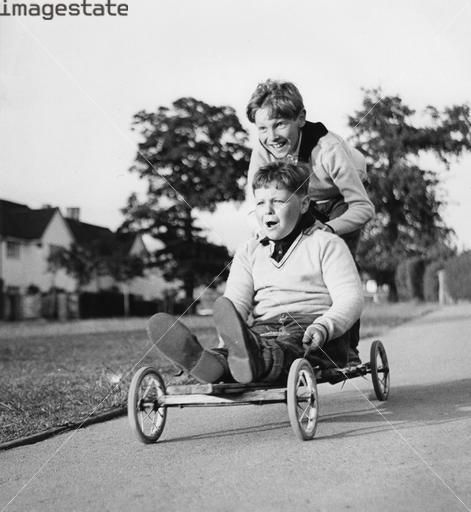 Boys playing with a home-made go-kart, My brother built his and entered it in our towns derby race.His name was Sonny. He did not win 1st place but he did ok.
