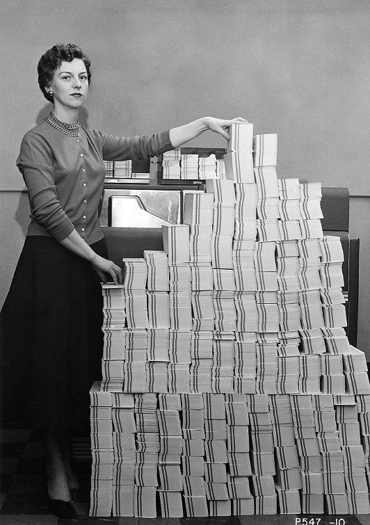 Programmer standing beside punched cards