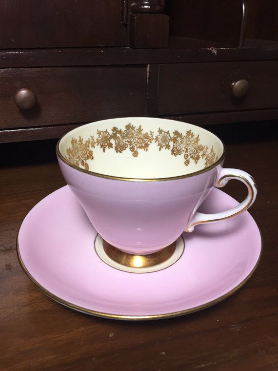 Royal Grafton teacup and saucer. Outer cup and saucer are bright pink with gold trim. Tea cup handle is white with delicate leaves painted in gold. Inside of teacup is cream coloured with a gold floral design around the rim. This set would compliment a formal table setting nicely.