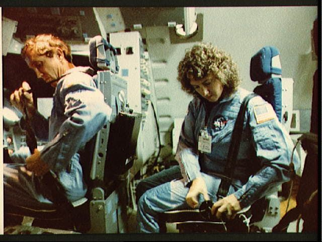 Christa McAuliffe and Mike Smith strapping themselves into position in the space shuttle simulator.  STS-51-L
