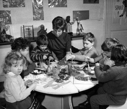 Op de kleuterschool : Zes kinderen / kleuters zijn lekker aan het knutselen aan een  ronde tafel in een lokaaltje van een kleuterschool. Hun kleuterjuf zit in het  midden. Nederland, [1963].