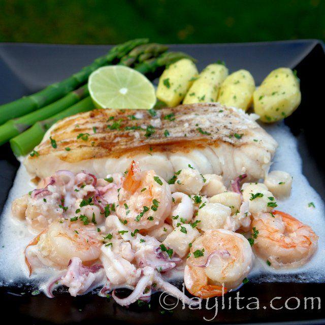 Pescado asado o pescado a la parrilla en salsa de mariscos al ajillo preparada con camarones o gambas, calamar, vieiras, ajo, cebolla, vino blanco y crema.