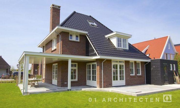 Jaren 30 villa met verspringende goothoogte, rode bakstenen, donkere pannen en witte kozijnen te Delft