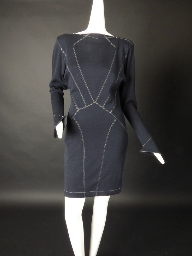 Awesome early 1990s dress in a black wool knit with decorative white top stitching and silver metal brads on the shoulder next to the neckline and at the fluted cuffs. Diagonal back zipper closure. Co