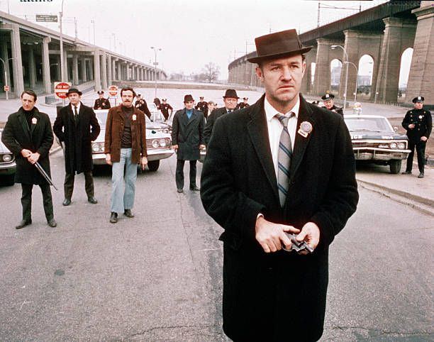 American actor Gene Hackman as Detective Jimmy 'Popeye' Doyle stands in the street by an overpass in front of a group of policemen and holds a gun in...
