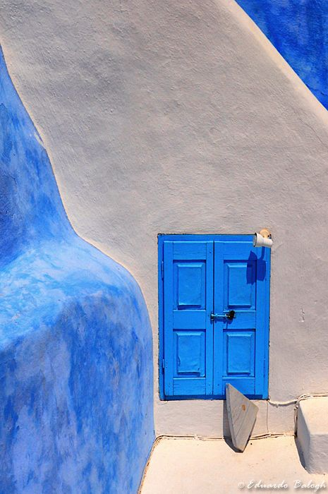 Santorini, Greece. Beautiful blue colored doors on stonewashed white buildings & churches!