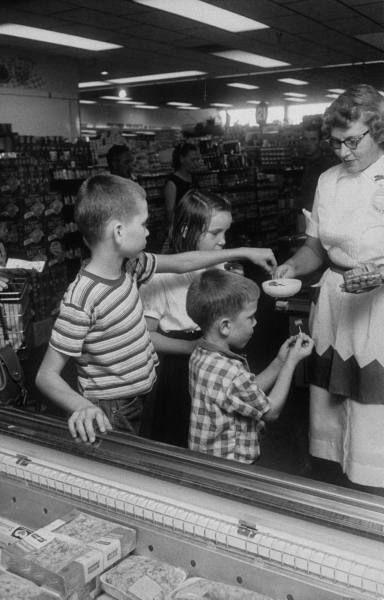 Company saleswoman giving out samples of frankfurters in supermarket to children, September 1957. #vintage #supermarket #shopping #1950s