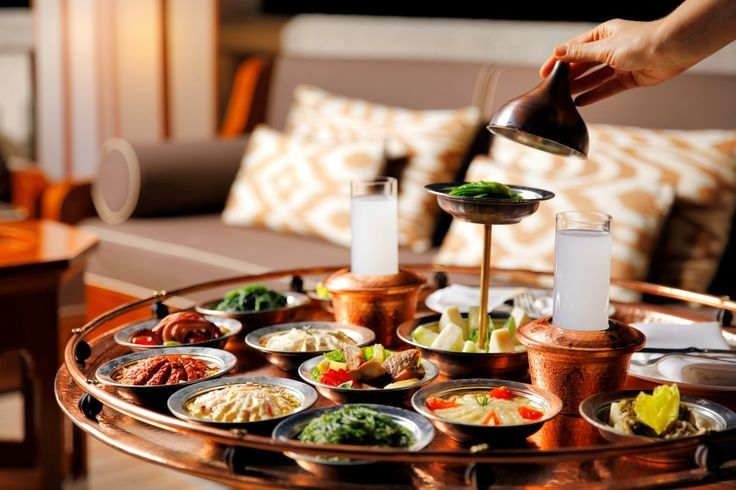 "A real Turkish dining experience: ""Çilingir Sofrası"". A glass of Turkish traditional alcoholic drink, Rakı, surrounded with delicious hot/cold meze plates."