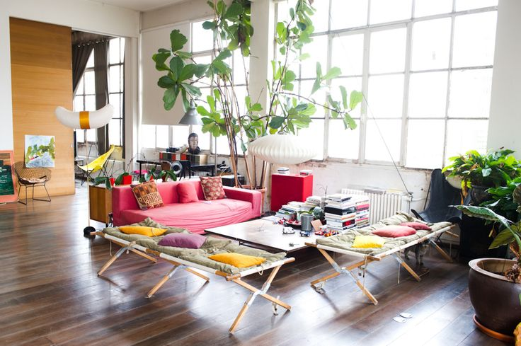 Eclectic, bohemian loft. Love the pops of colour, greenery, natural light, timber floating floors & stretcher beds come casual seating.