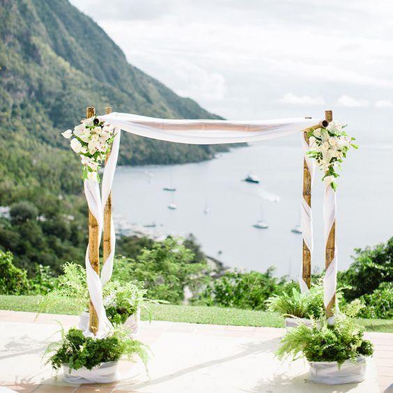 Un arco de flores para bodas con bambu con tela entrelazada y arreglos de flores blancas creado por Jardin Tropical. Toma nota del paso a paso!