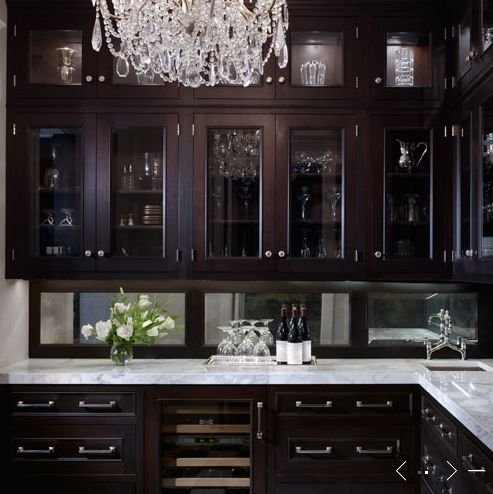- butler's pantry crystal chandelier glass-front espresso stained kitchen cabinets marble countertops sink bridge faucet Butler's pantry design