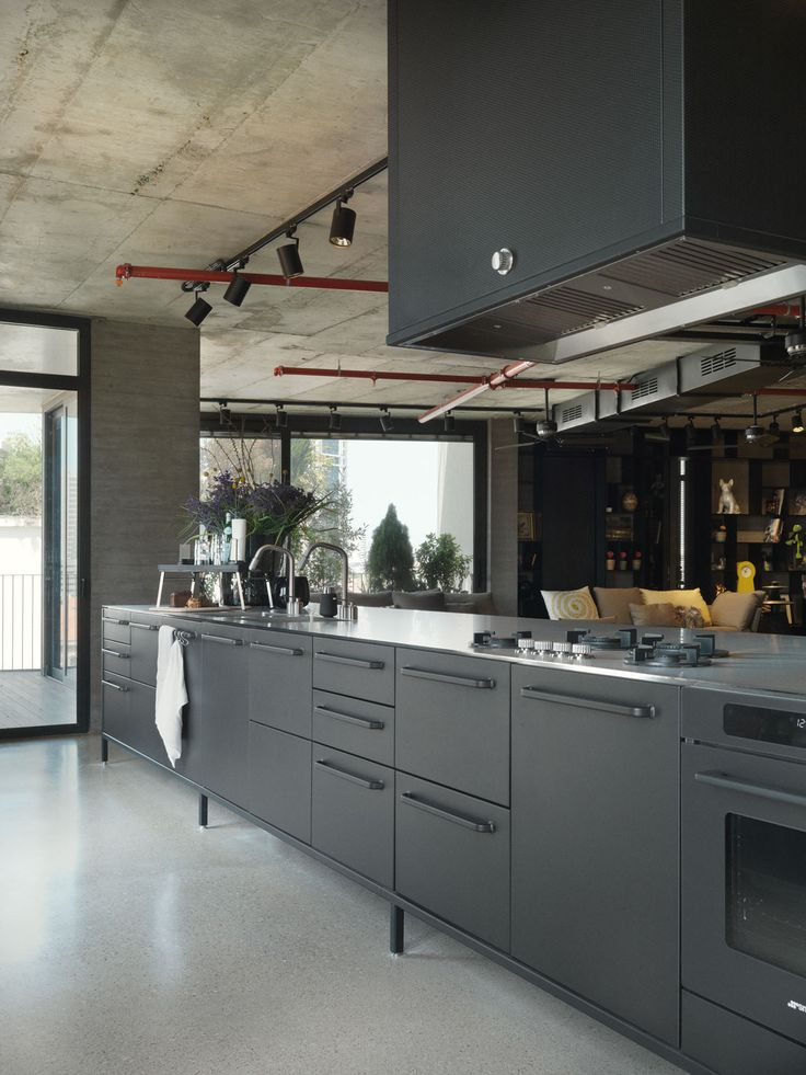 Large black Vipp kitchen in an open plan apartment in Tel Aviv