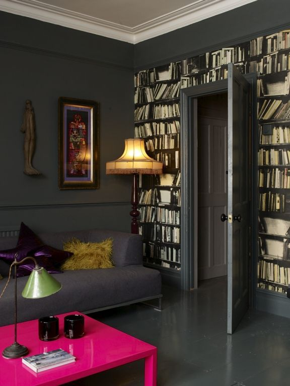 bookshelf wallpaper - the real thing would be ideal, but I guess this is better than nothing! And I love that chandelier lamp shade. It's very Christmas Carol-esque. And hello, pink table. Talk about a statement!