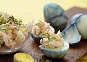Dekorativ anretning med æg til påskefrokost: rejesalat i blålige solæg.