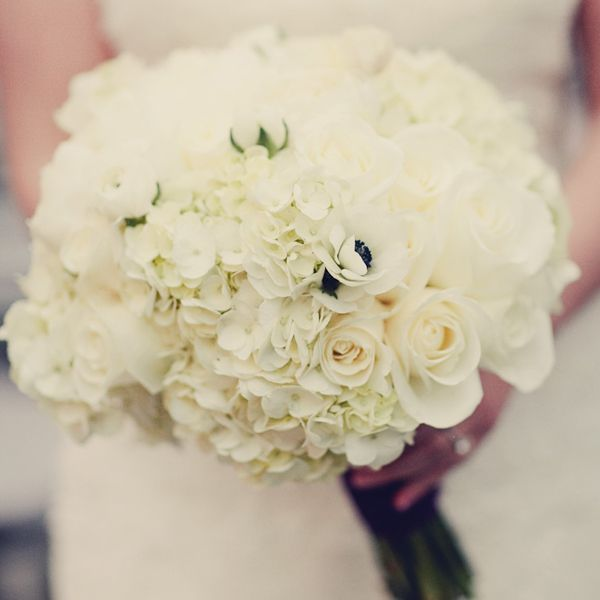 An all-white bouquet of hydrangeas, peonies, roses, ranunculus, and anemonies