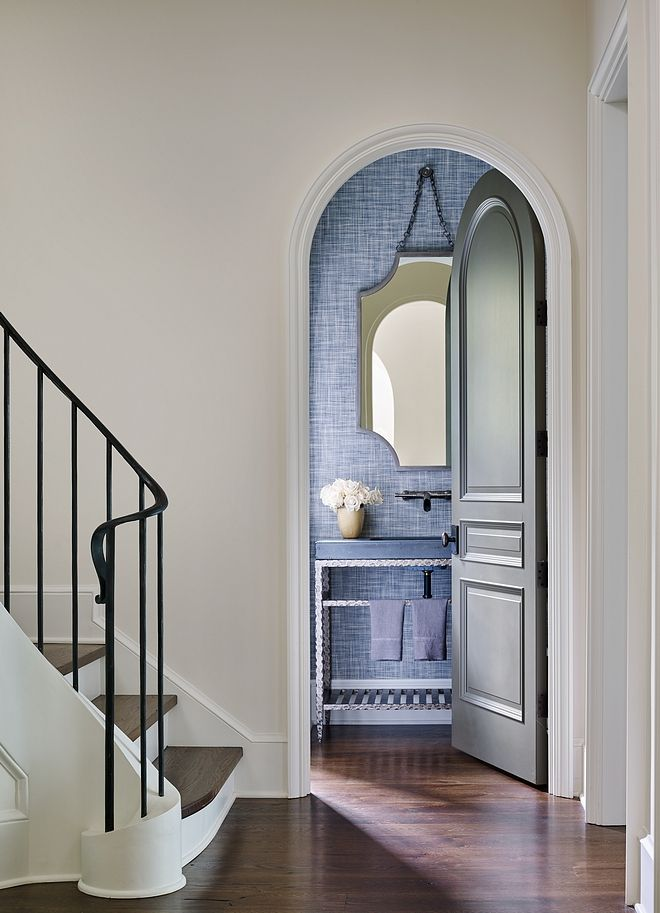 Powder room located off foyer with arched doorway