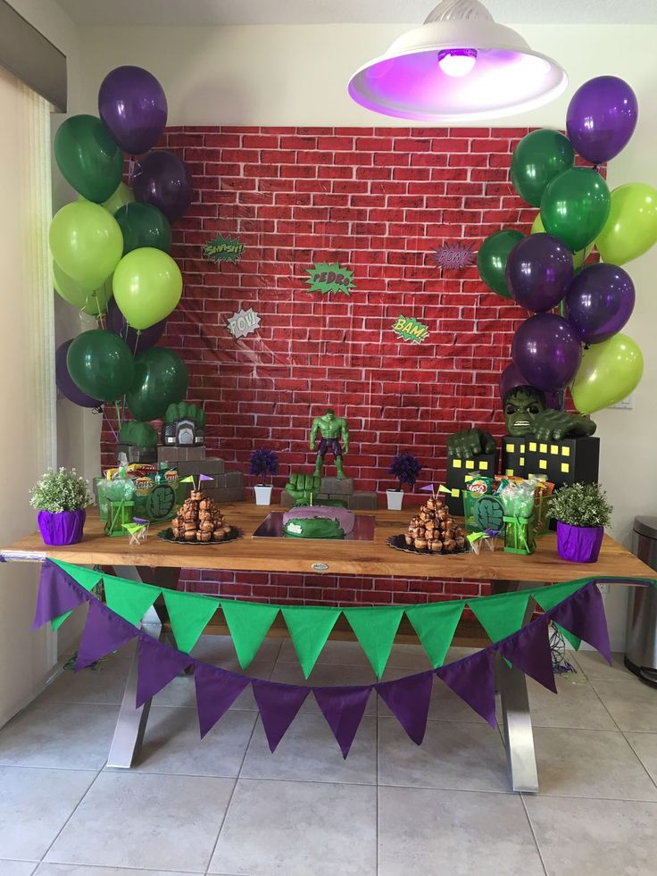 Light green. Dark green. Purple balloons.  Box buildings. Hulk hands on top Hulk cake in middle