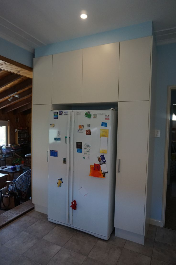 Fridge space with pantry on either side Upper cabinets fitted with touch catch and handles on the lower doors