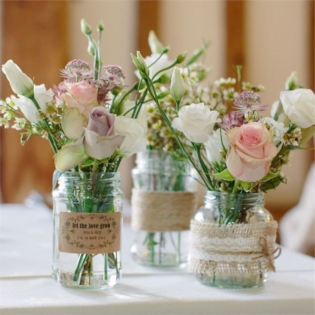 Rosen und Wicken in Glasvasen mit Spitze und Jute