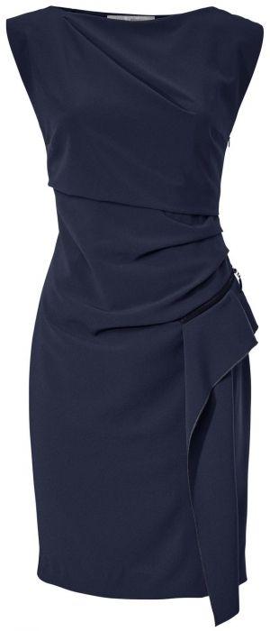 Ein schickes Kleid in Dunkelblau mit einem schicken Wickeldetail. Ein heller Blazer von Only und Pumps von Tamaris ergänzen das Businessoutfit für die Dame elegant.