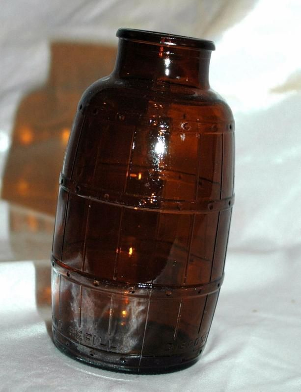 Vintage barrel shape Schmidt beer bottle in amber glass    The twelve ounce bottle is shaped like a barrel and even has embossed staves and bands on the glass.     Measures 5 1/2 inches tall, 2...