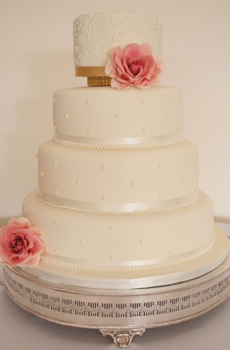 4 tier bespoke Wedding cake with handmade sugar roses and lace details to the top tier.