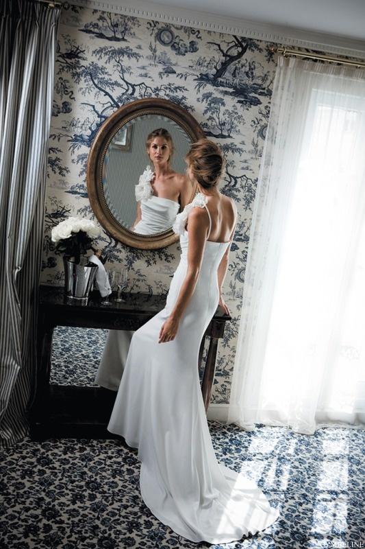 Suknia ślubna z ozdobnym kwiatem.