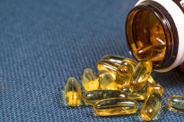 fish oil capsules with omega 3 and vitamin d in a glass bottle on