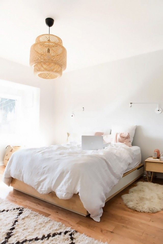 Bedroom with a woven chandelier and neutral bed linens