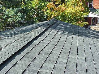 Peak of roof with ridge vent and asphalt shingles nailed over vent material.