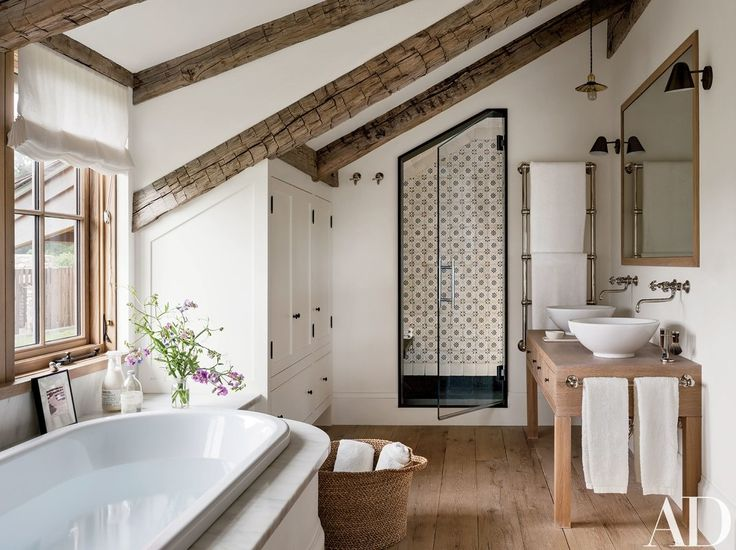 In the master bath, Lacava basins are paired with Waterworks sink fittings; the shower is lined with Exquisite Surfaces tile | archdigest.com