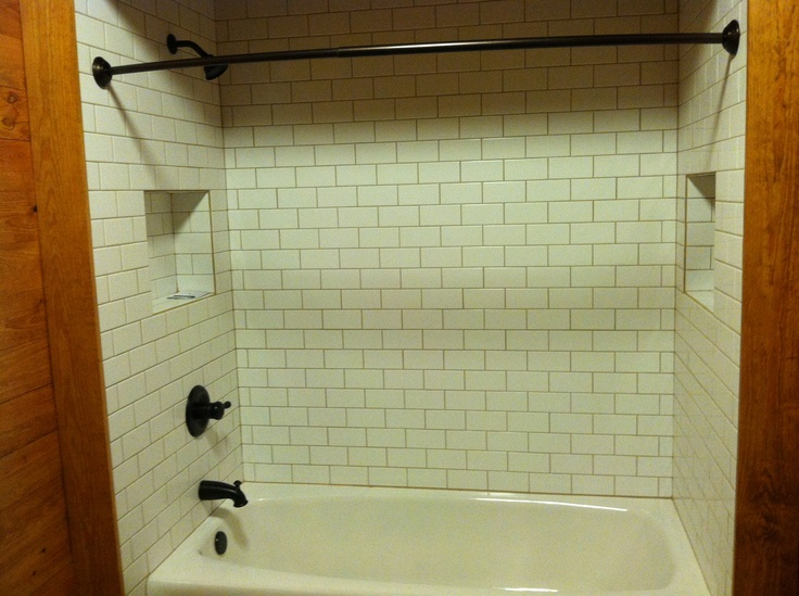 """New shower with 3""""x6"""" subway tile over 66"""" cast iron tub with two soap/shampoo niches."""