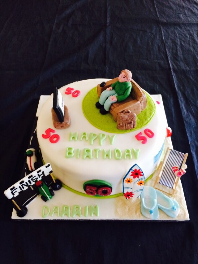 A 50th birthday cake, man in chair watching tv, with his interests surfing and beach and f1
