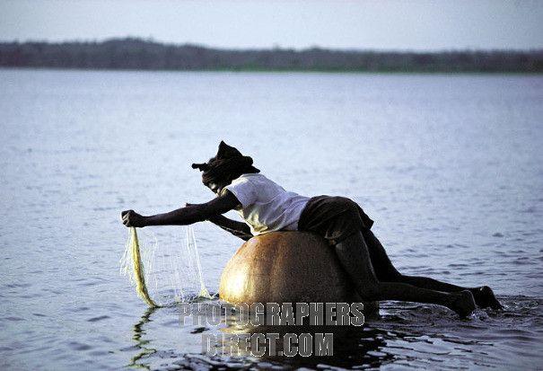 a Gwari man checks his fishing net while floating on a gourd , near Minna , Nigeria stock photo